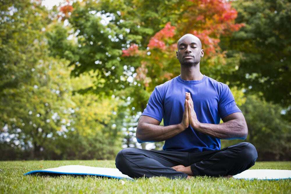 A man practicing yoga in the park