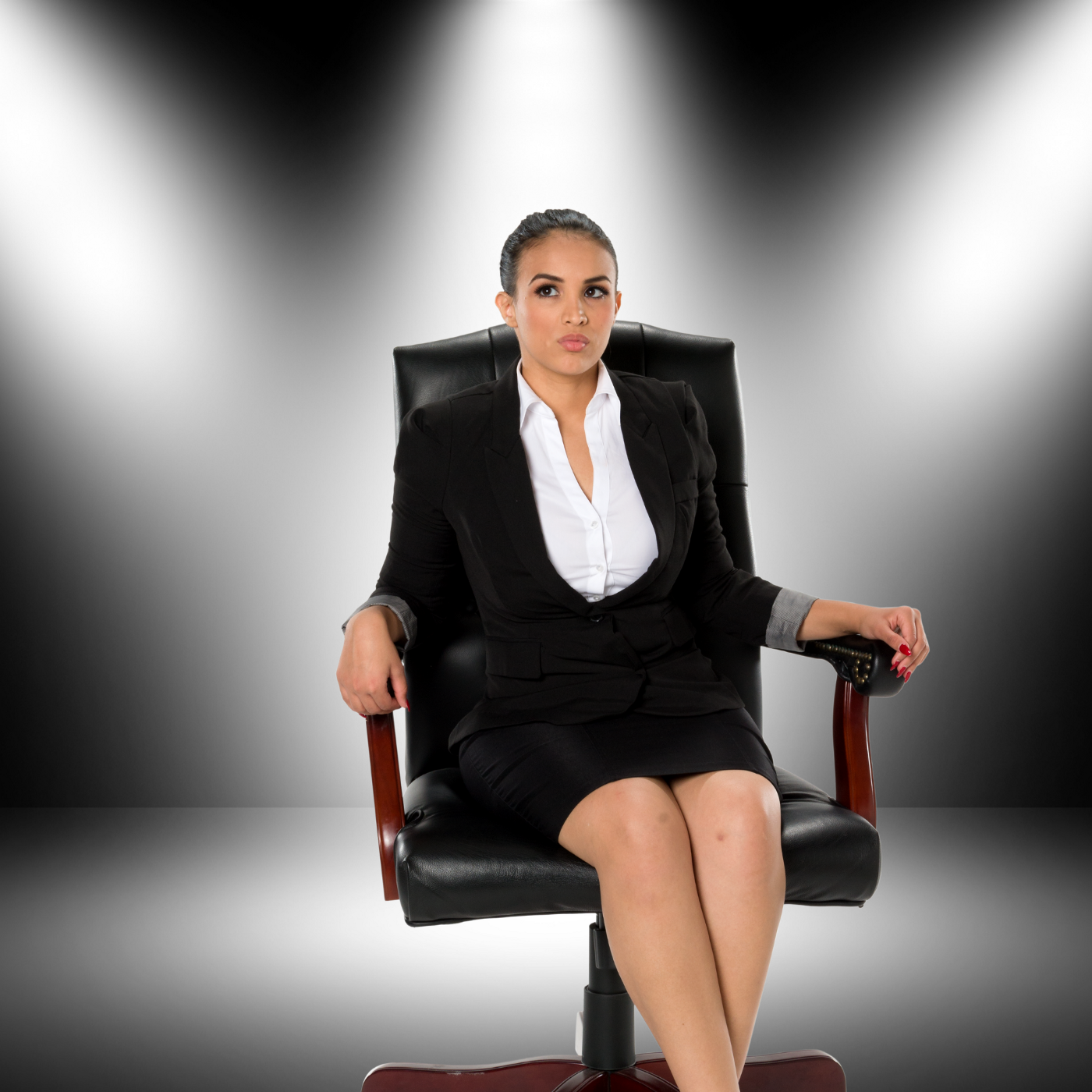 Woman sitting in an office chair on stage under spotlight.