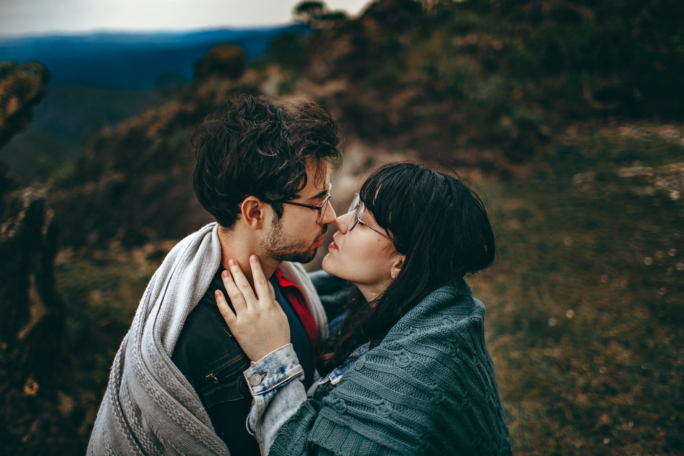 A couple on top of a mountain who are embracing and just about to kiss. They both have blankets around their shoulders.