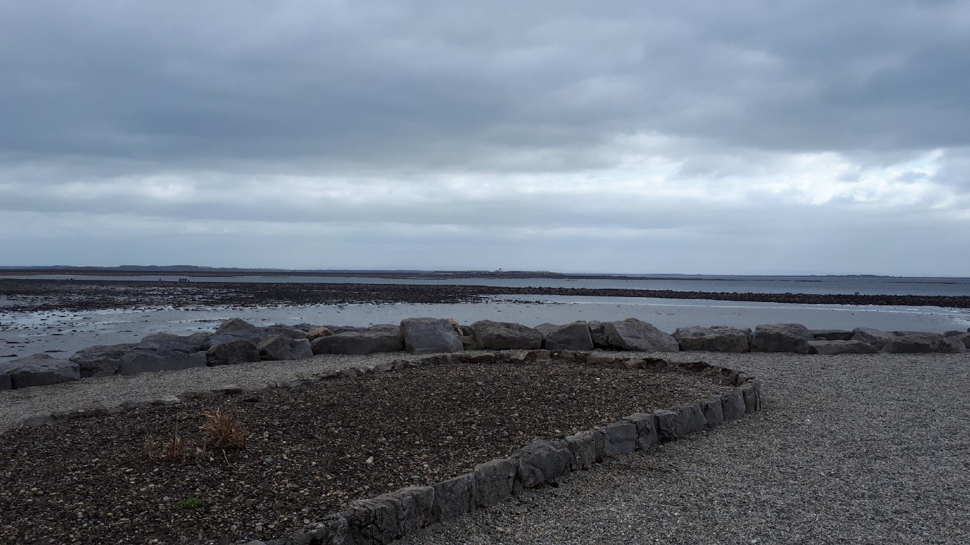 A barren garden of tilled earth in the foreground with a low ocean scene in the background. The sky is grey and cloudy.