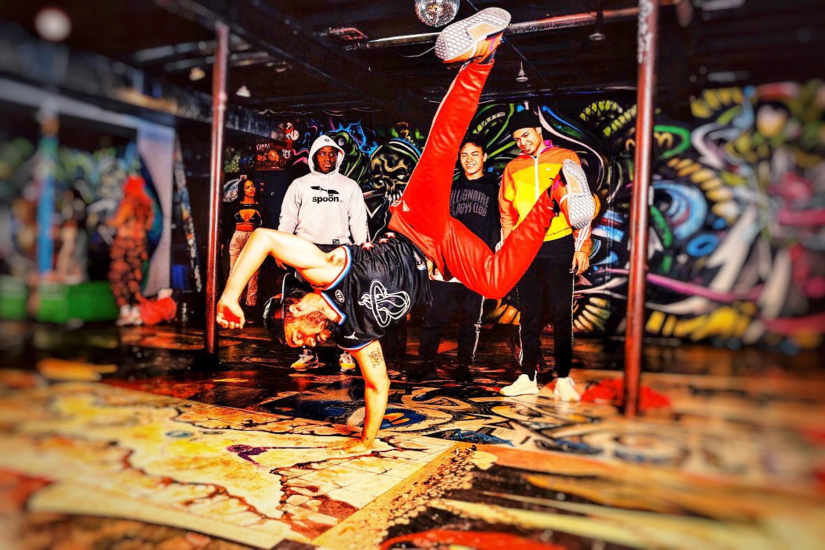 A break-dancer on a stage and others standing around watcching. There is a lot of artistic grafiti spray painted all over the walls