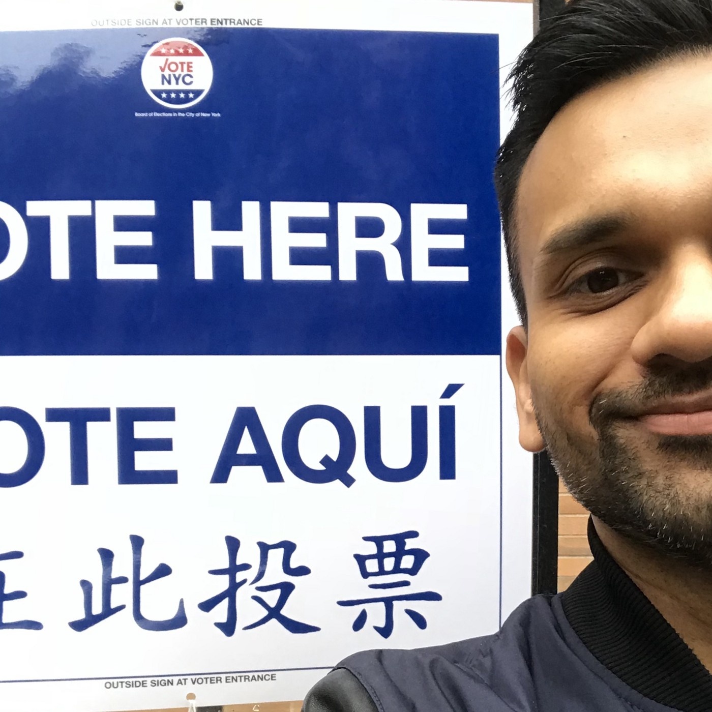 Anu is standing next to a Vote Here sign and smiling