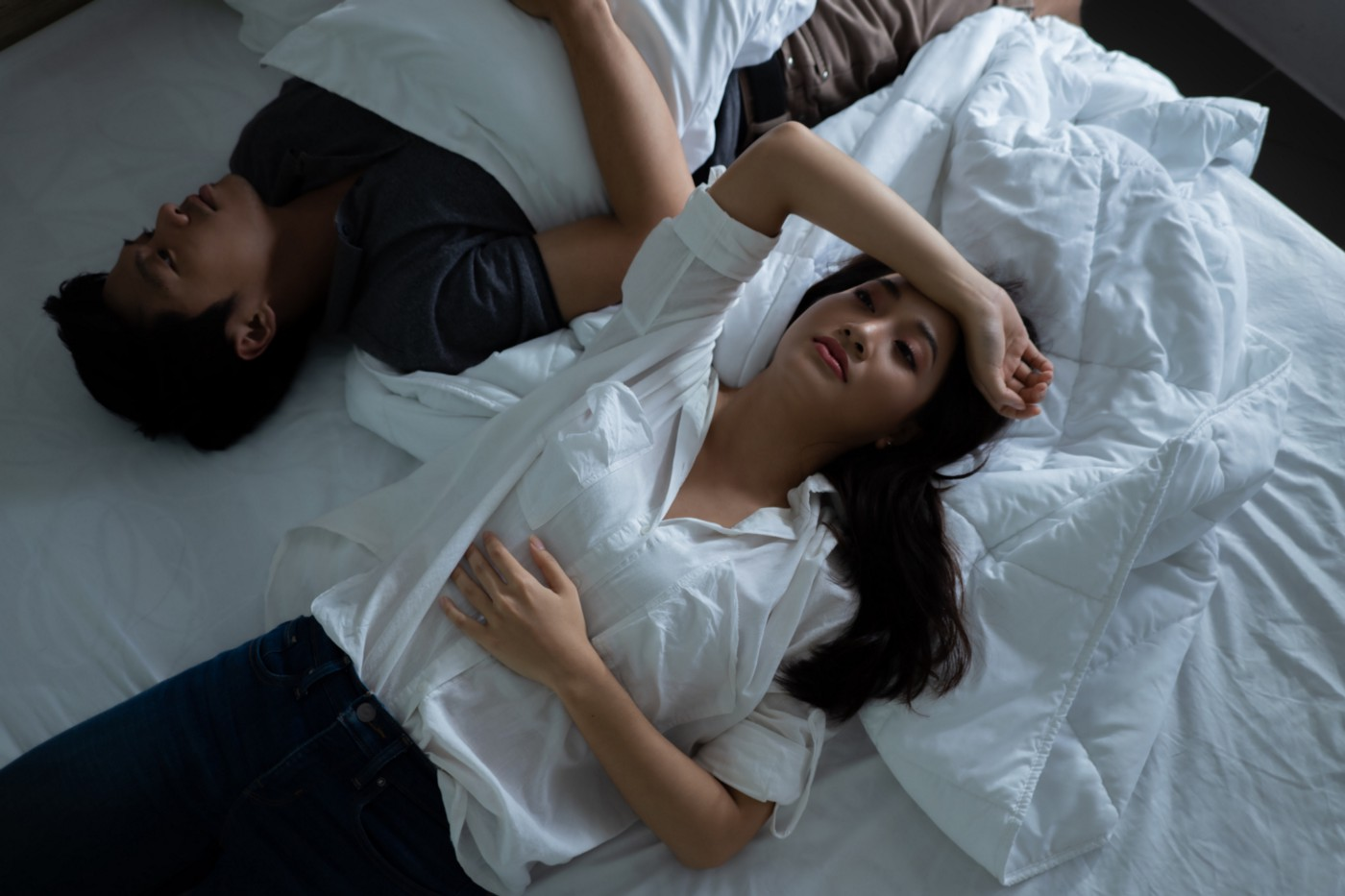 A stressed couple lying down on the bed and staring at the ceiling.