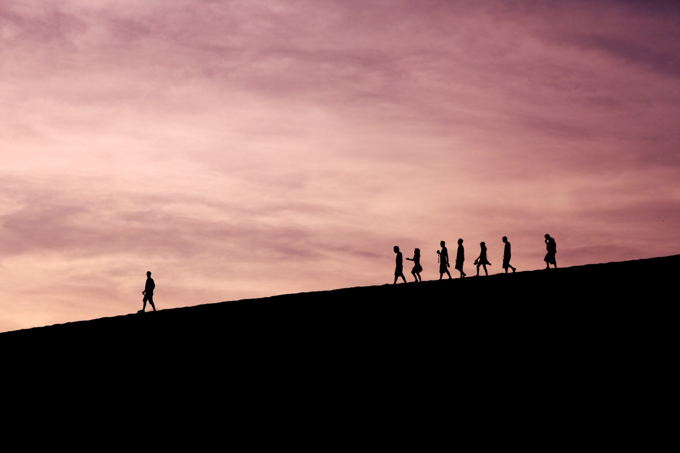 Silhouette of people walking along a ridge with a pink sky behind