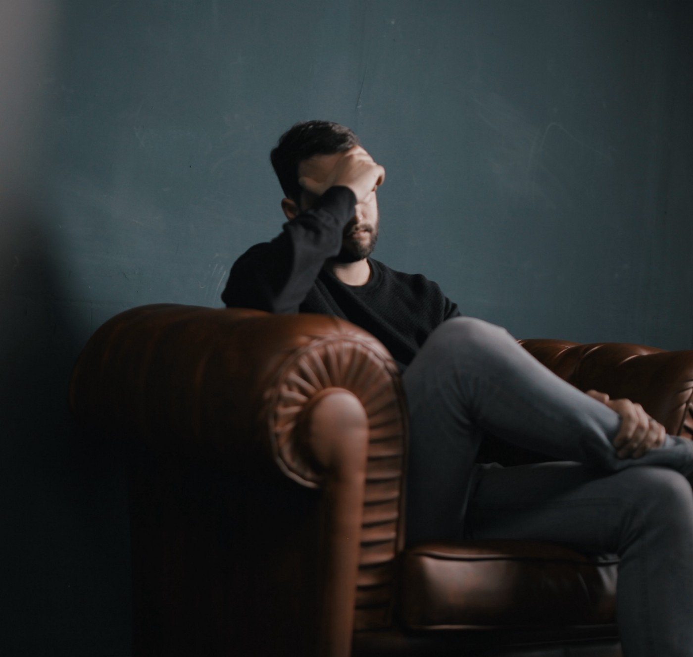 A dark mood/color palete photo with a young man sitting on a brown chair, with his head in his right hand in a forlorn fashion.