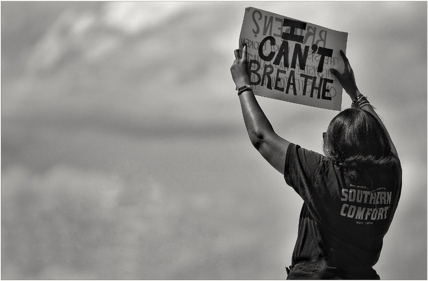 A woman holds up a sign reading 'I can't breathe'