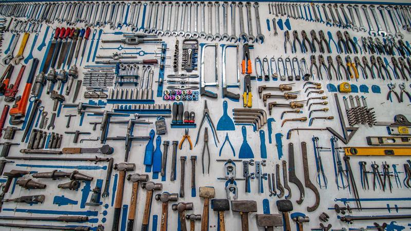 A number of different kinds of construction tools laid out on a floor.