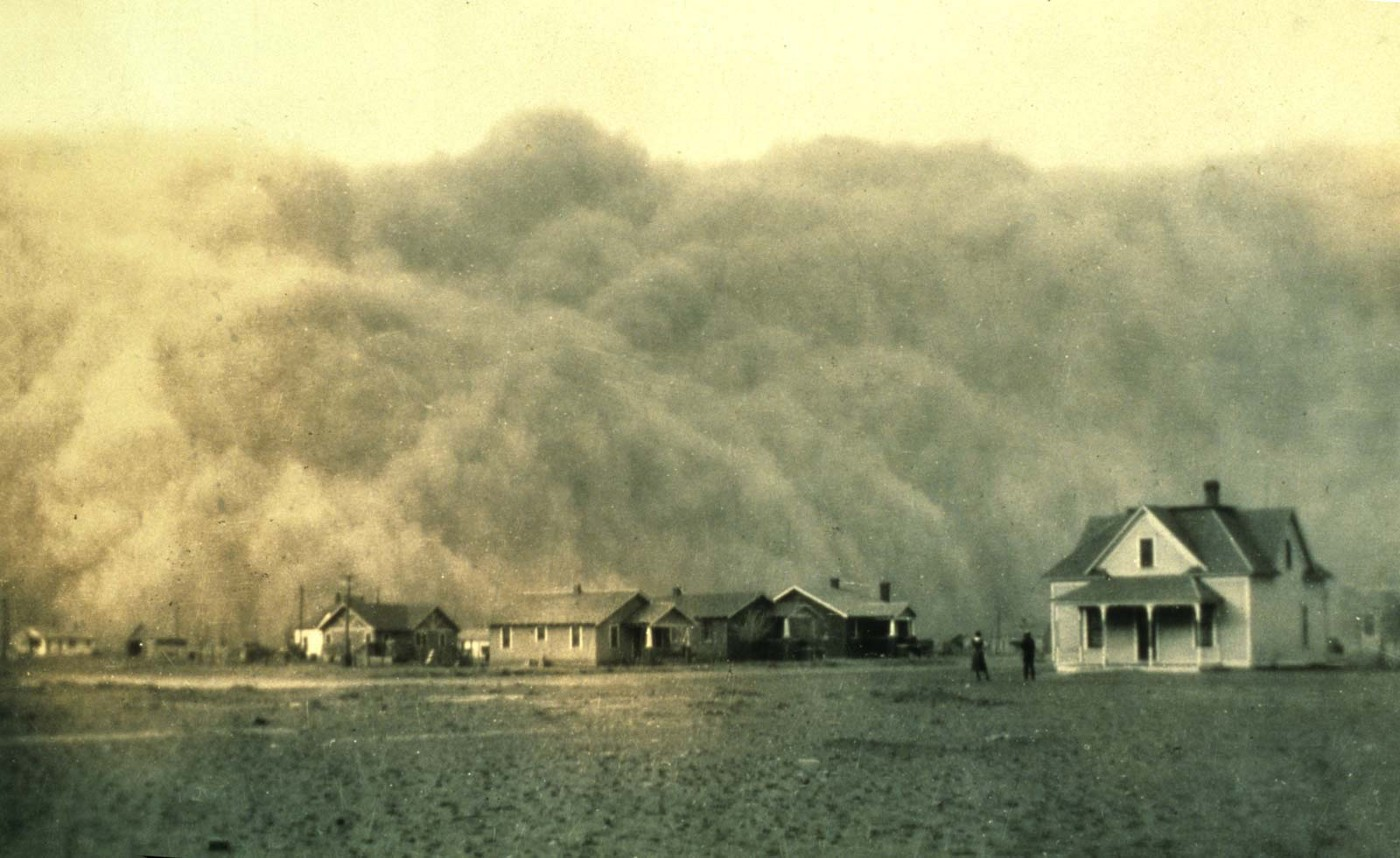 An antique photo of a dust cloud overtaking a small family farmhouse, with barren fields in the foreground.