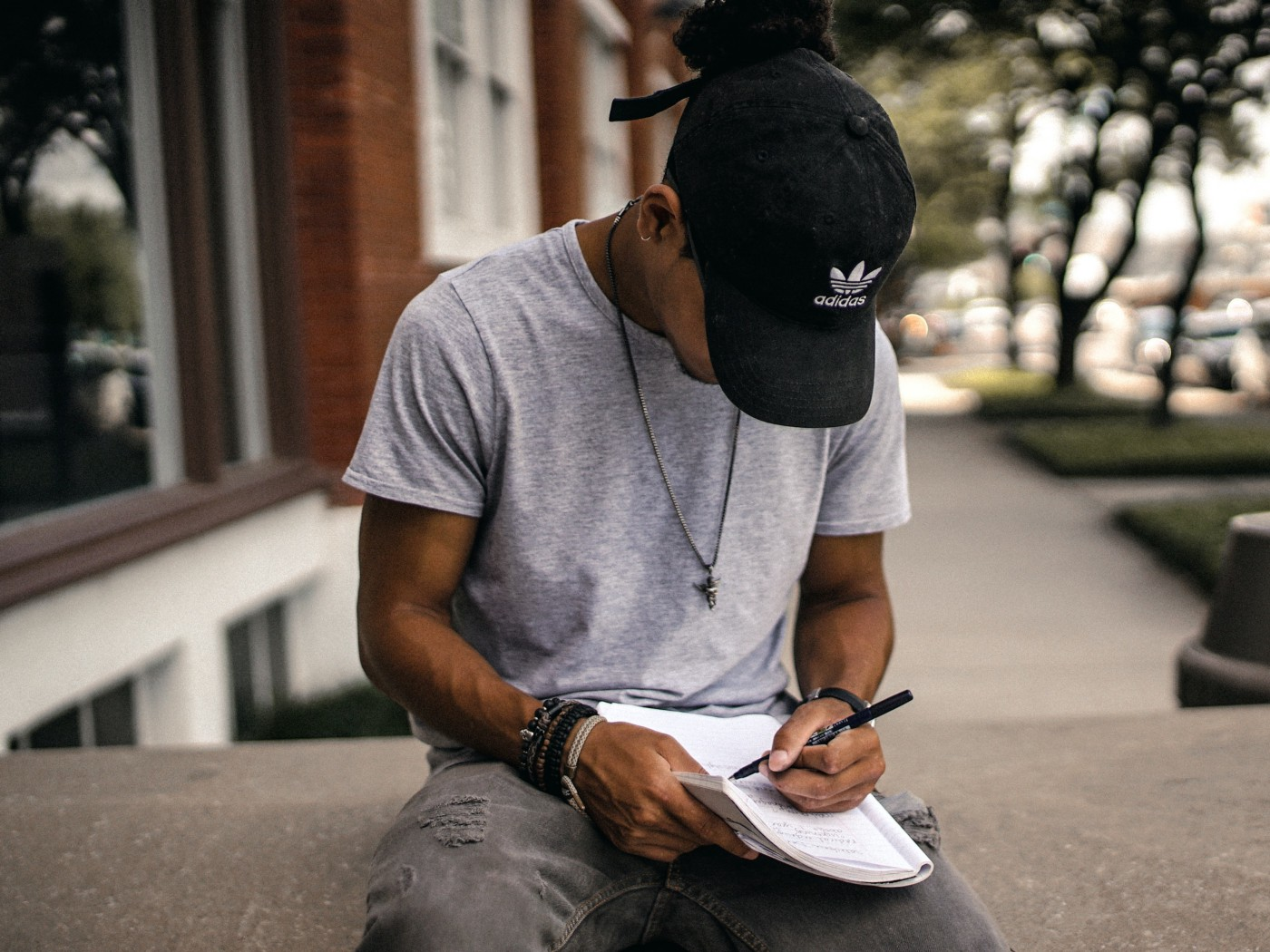 Black man sitting down writing in a notebook