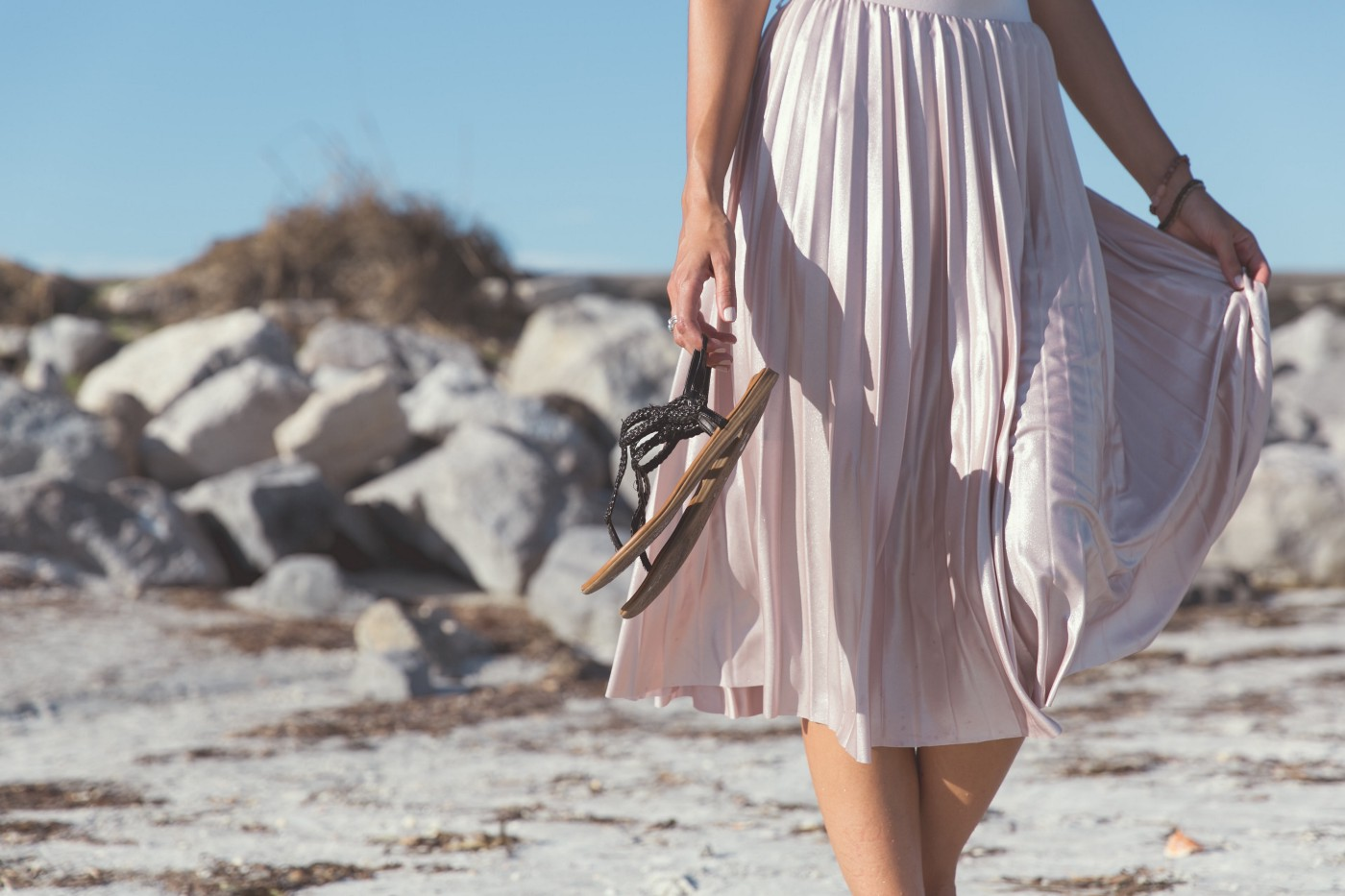 White woman in pleated pink dress shown from the waist down, carrying sandals, her bare arms and legs below knees showing as she walks on a sandy beach.