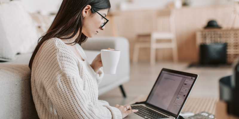 Woman drinking coffee and writing on a laptop—7 Google Tricks To Find Better Keywords