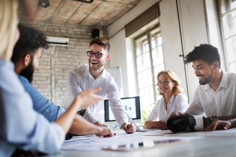 A group of business people sit around, satisified with their employment. How? They followed Acorn Labs extensive of guide on measuring and improving employee satsifaction.