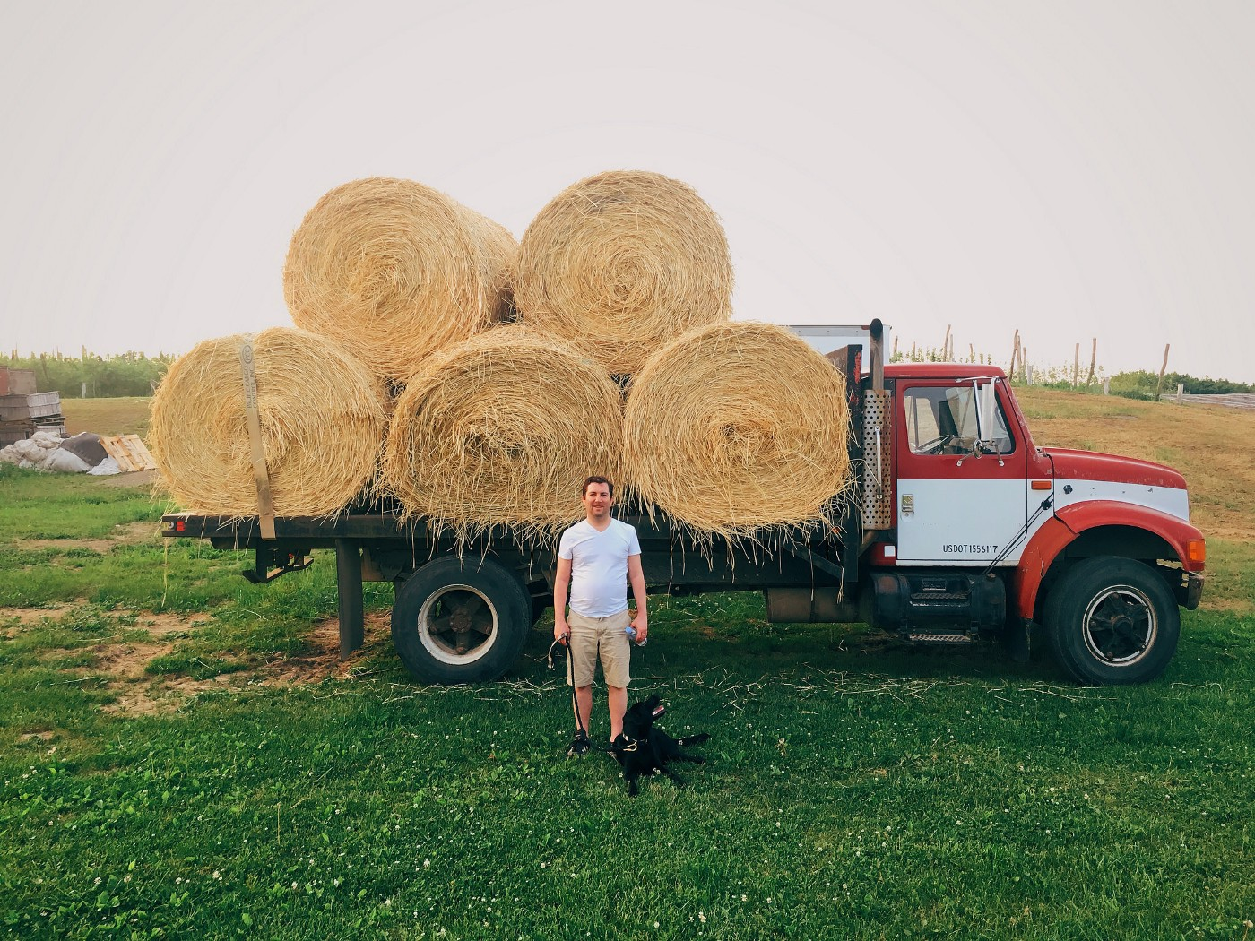 Mat Zucker and his dog Nora in front of a hay truck for the Cidiot podcast