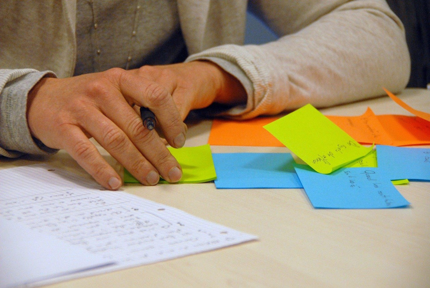 Person organization thoughts with post it notes and paper