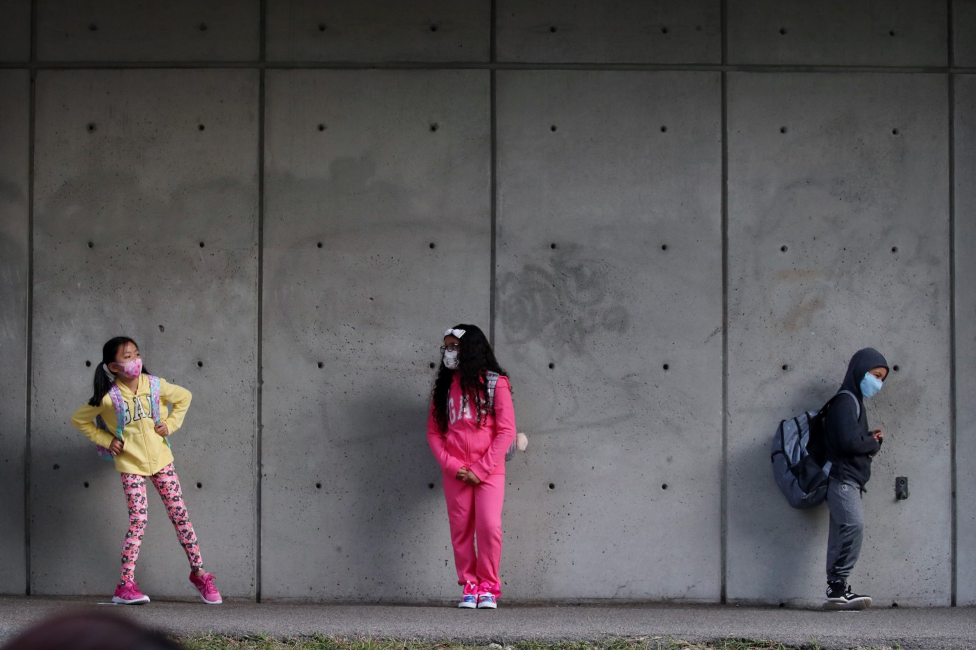 3 elementary school students wearing face masks and standing against a cement wall, 6 feet of distance between them.