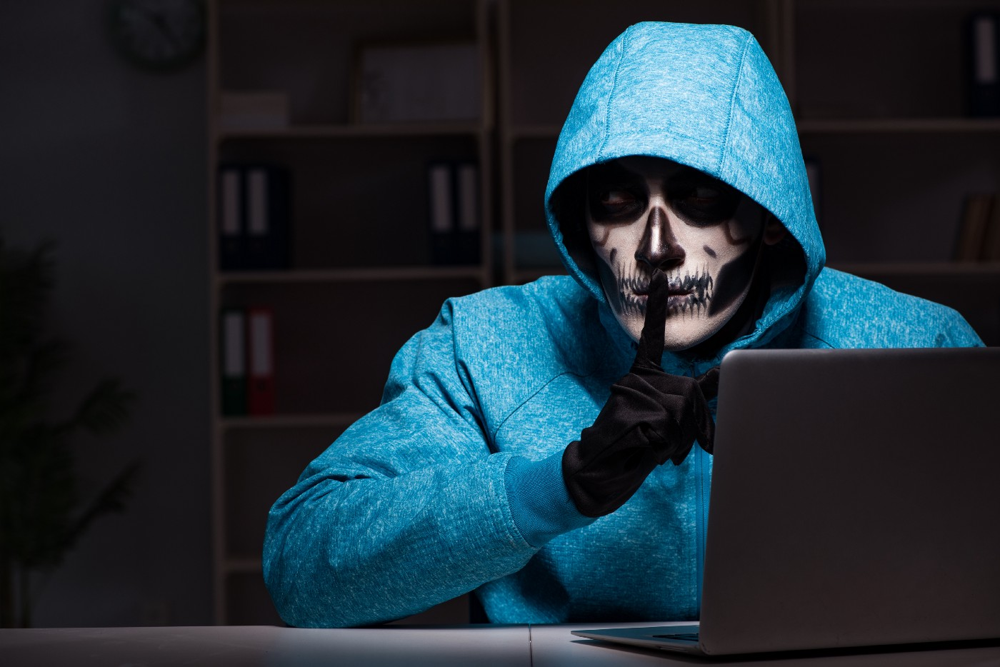 """A person with skeleton face paint in a hoodie in a dark library behind a laptop, with their finger in a """"shh"""" position."""