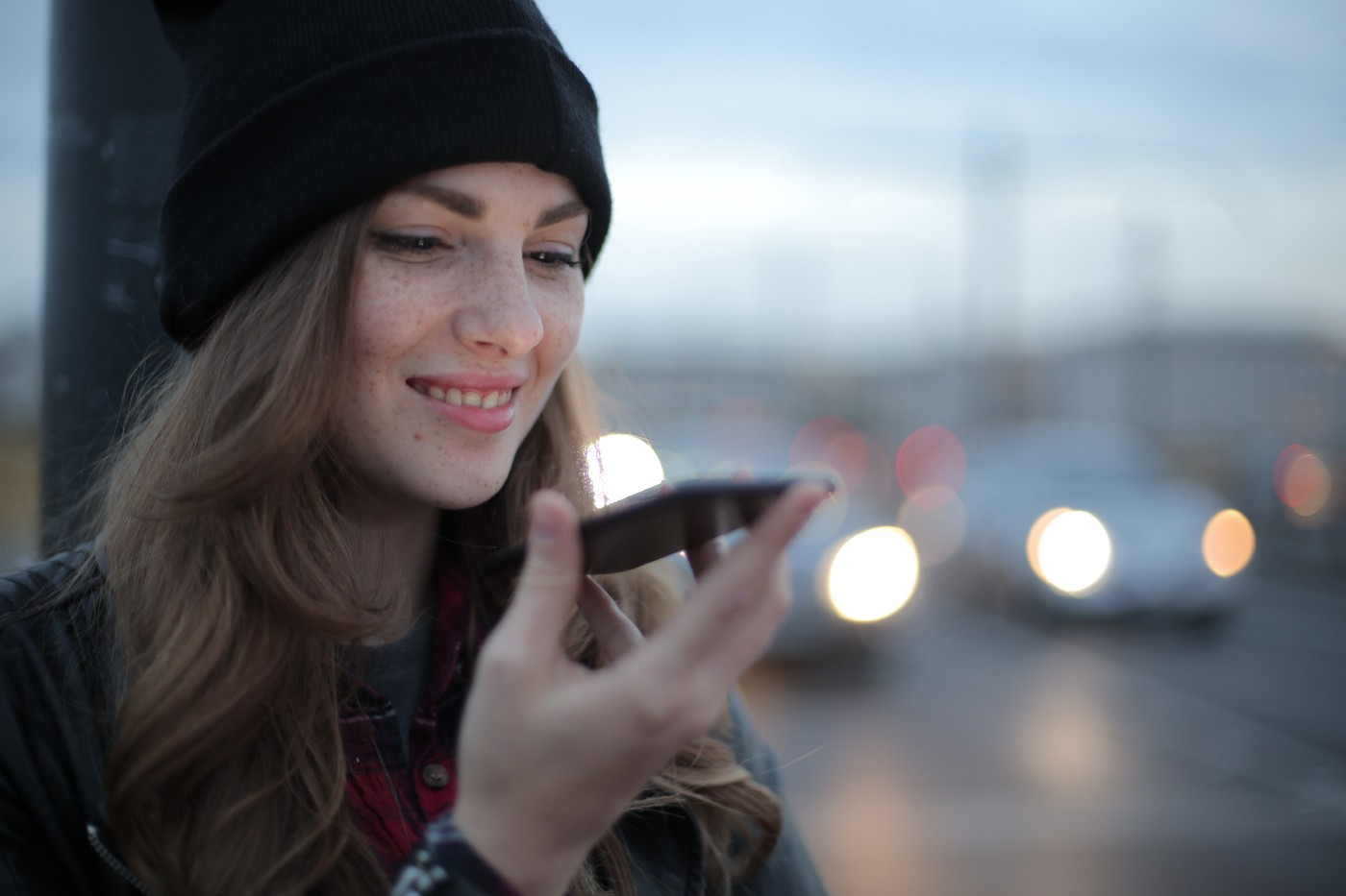 Girl with black hat on holding phone up and smiling with busy street of cars in the background