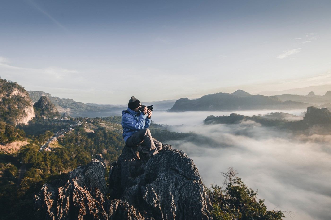 Man on top of a mountain taking photos Image: unsplash.com