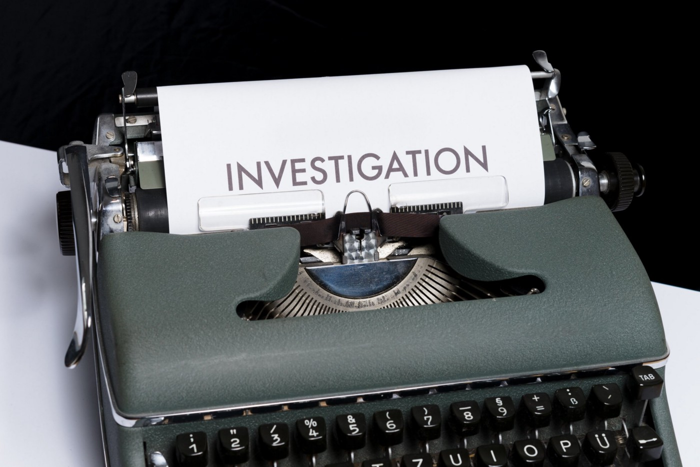 """[image description: a gray typewriter with a paper inserted that says """"investigation.""""]"""