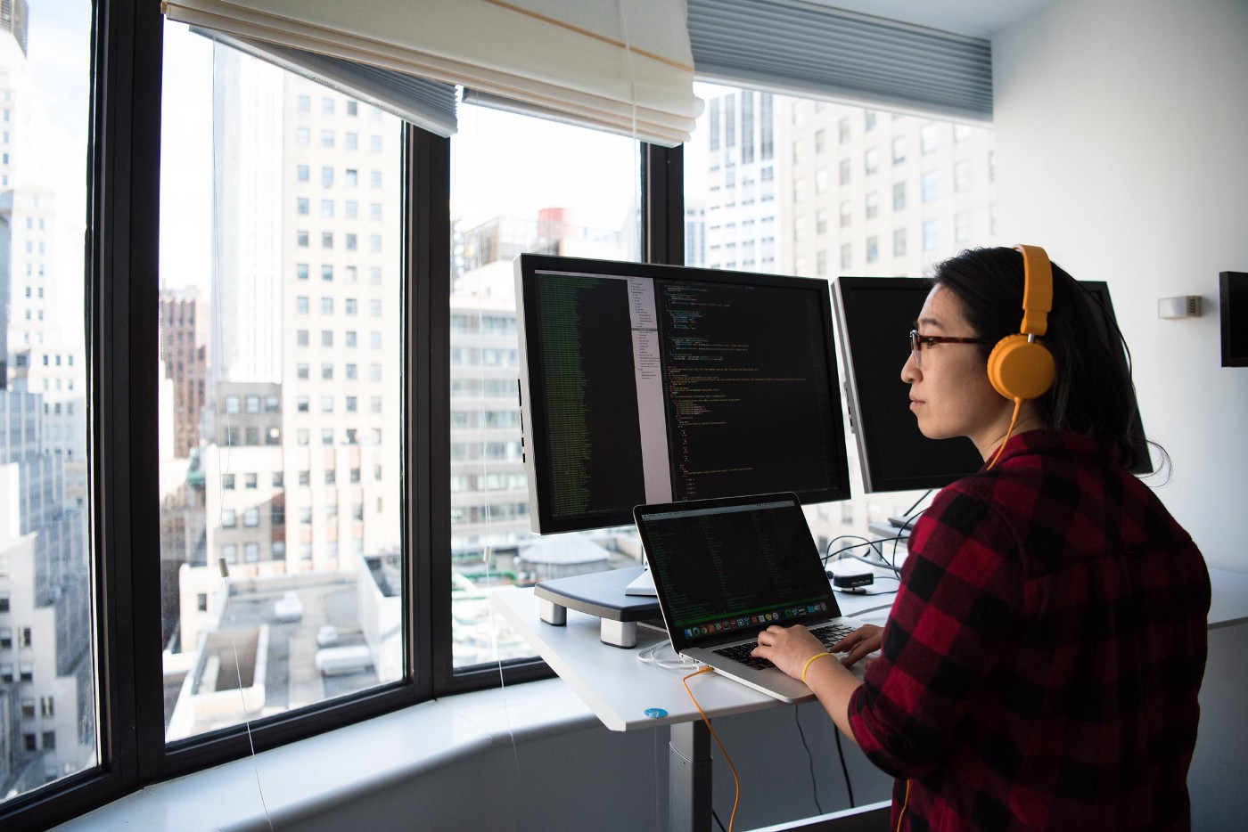 A woman looks outside the window of a high-rise building while sitting at a desk with her computers.