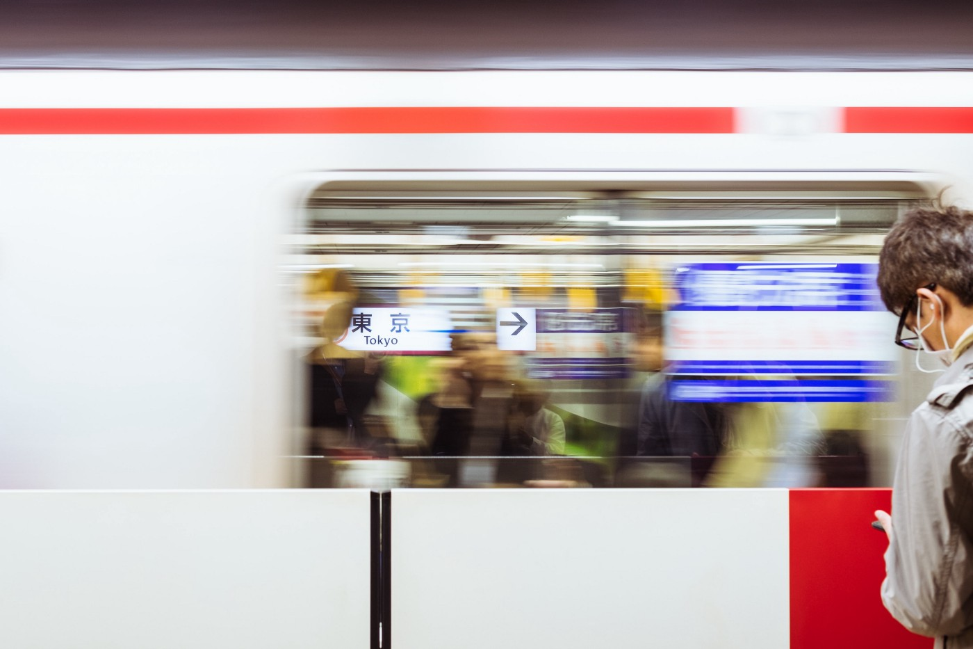 A man wearing a face mask looks at his phone while a train zooms by in the Tokyo subway.