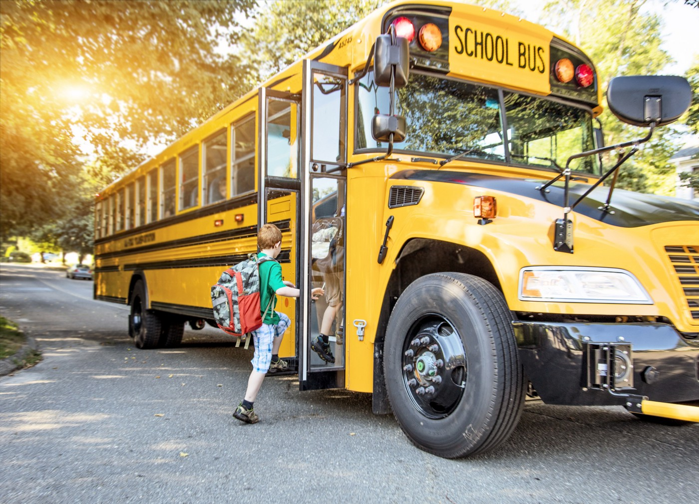 Boy with a backpack boarding a school bus