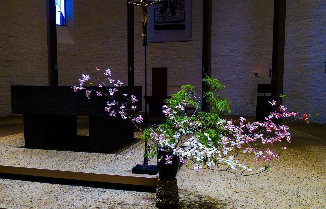 Altar in a church with crucifix on the side and display of dogwood in vase in foreground.