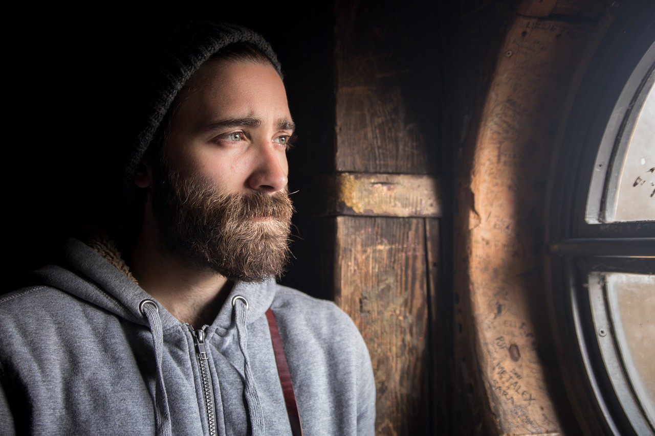 A man in a hoodie with a beard, looking out of an old window