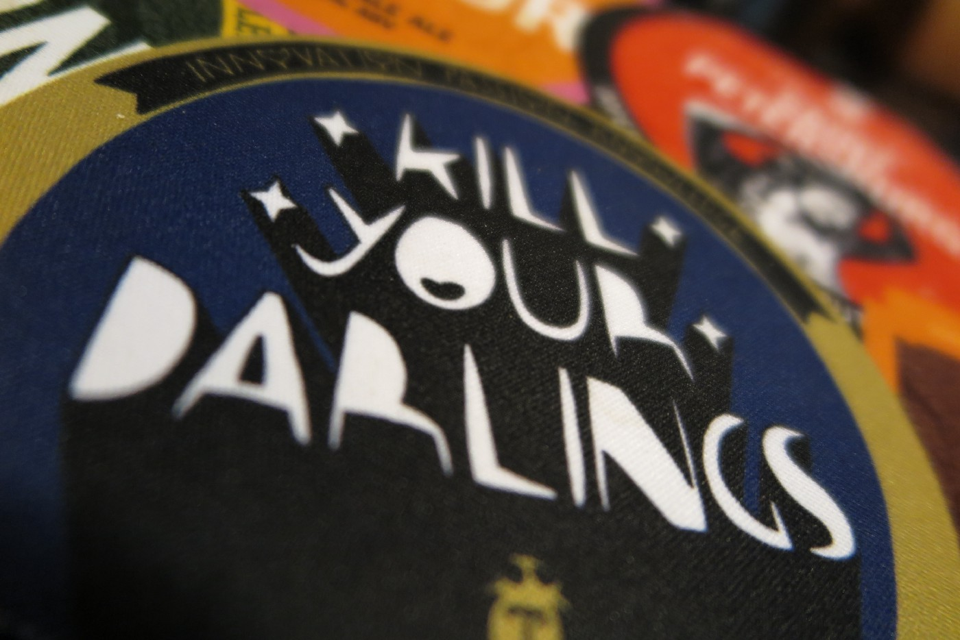 """Closeup image of """"Kill Your Darlings"""" text on beer label. White words on dark blue background."""