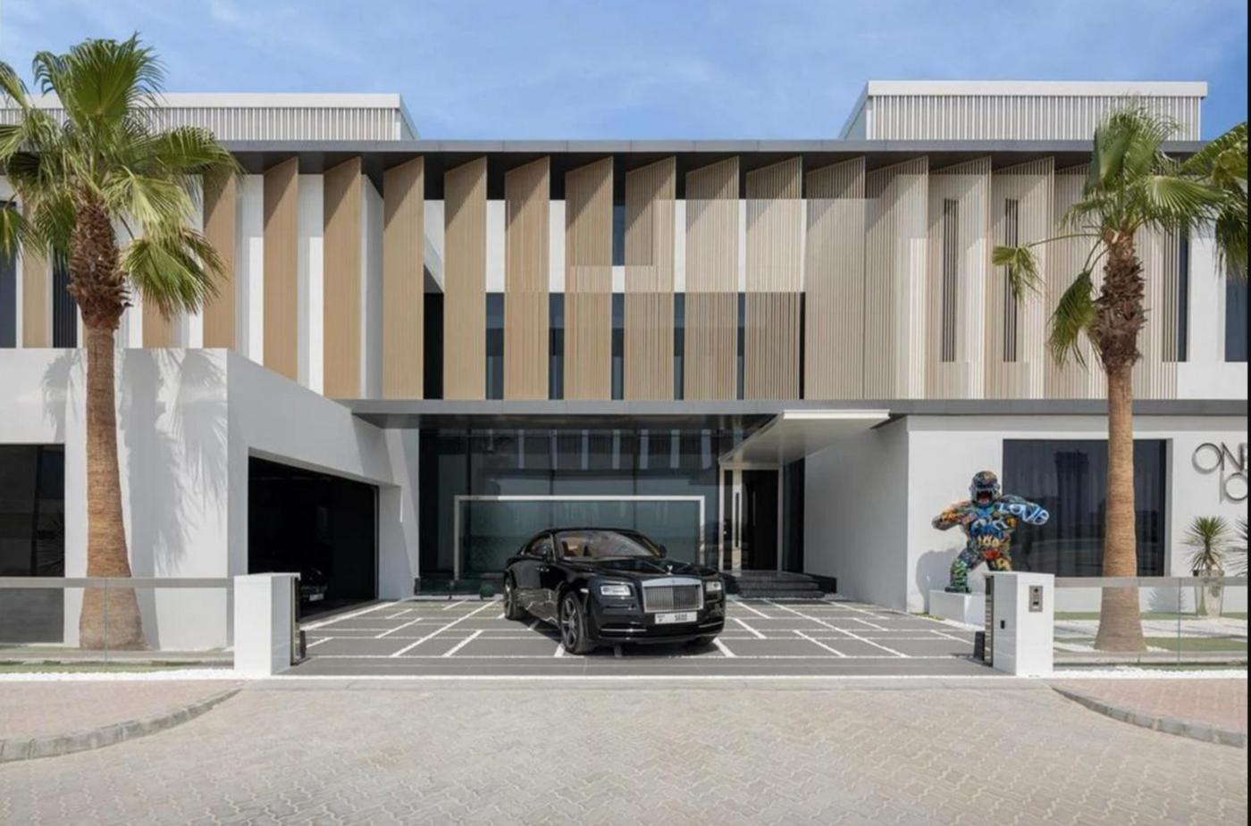 A cubist-inspired modern mansion with white walls, large square windows and large louvred panelling on the top floor. In the driveway sits a black Rolls Royce. To the right of the Rolls, there's a graffitied statue of a gorilla standing on a plinth. Blue skies and tall palm trees indicate that this house is somewhere hot.