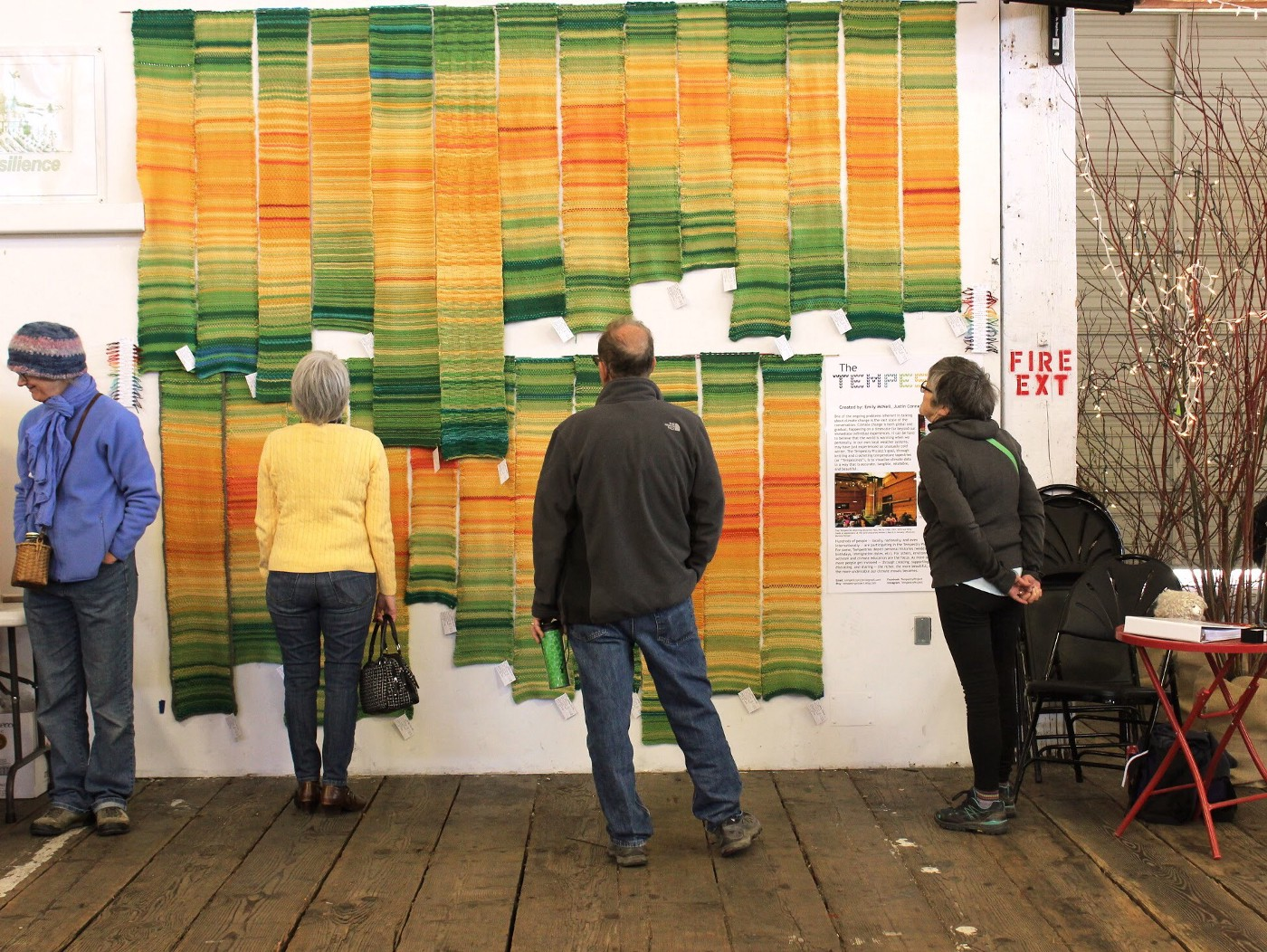 A collection of knitted Tempestries hanging vertically on the wall of a gallery.