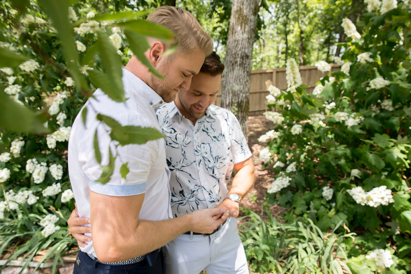 Two gay men in a wood; one giving the other a ring.