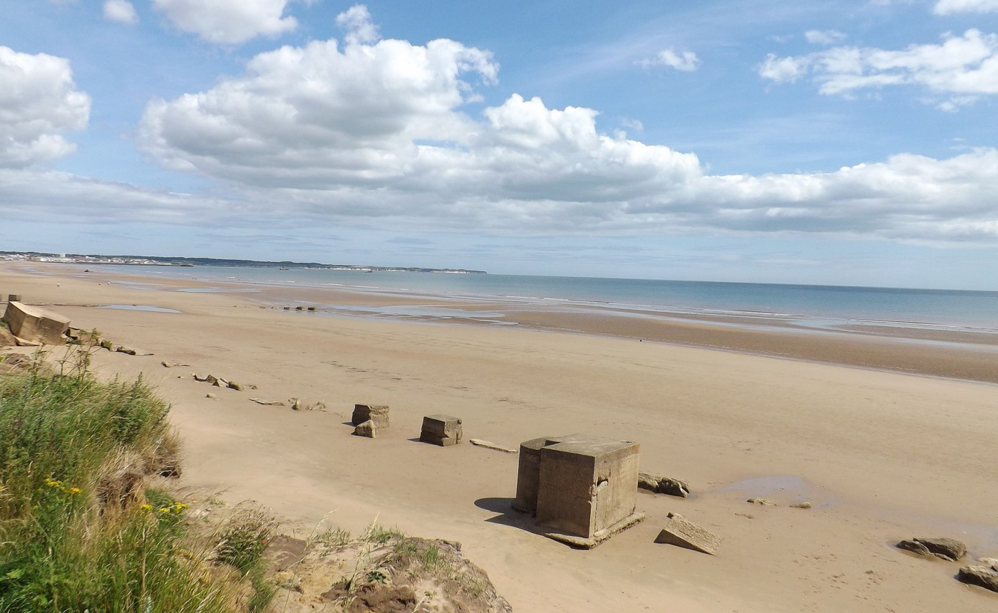 An image of Fraisthorpe beach, looking north towards Bridlington, where still there are reminders of the Second World War, with abandoned concrete pill boxes and anti-tank blocks placed among the sand dunes
