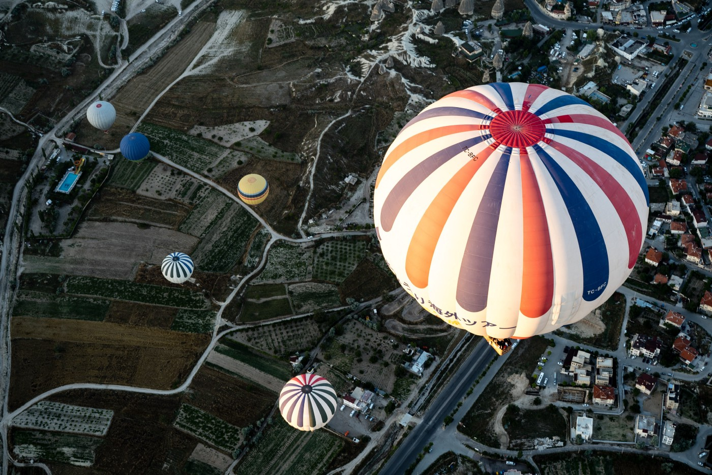 aerial view of hot air balloons hovering over a city