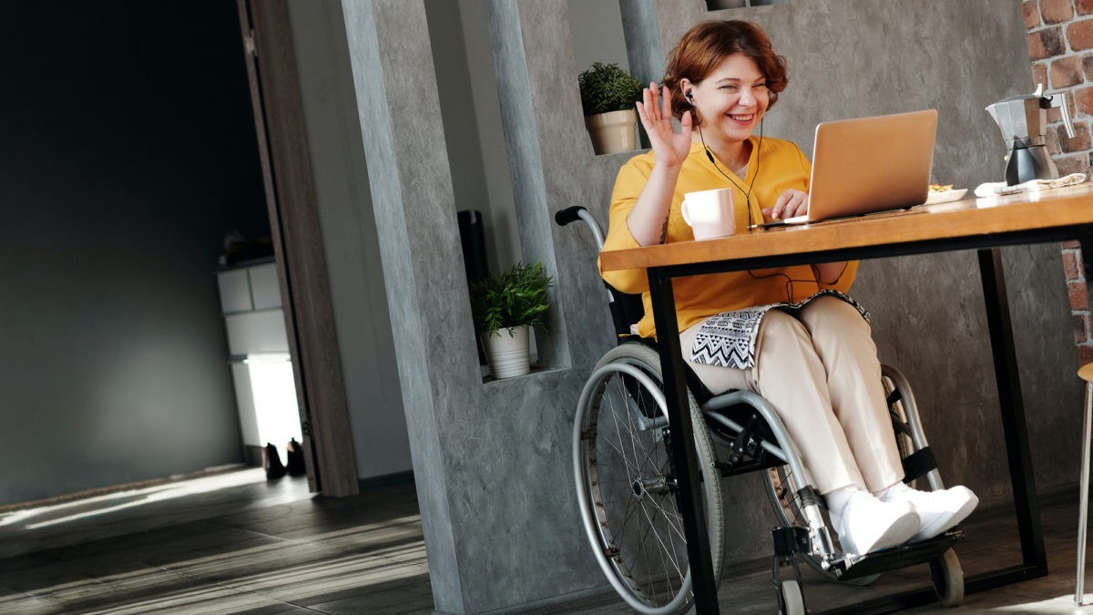 Image of woman sitting at a table in a wheelchair in front of a laptop. The woman is smiling with her hand raised