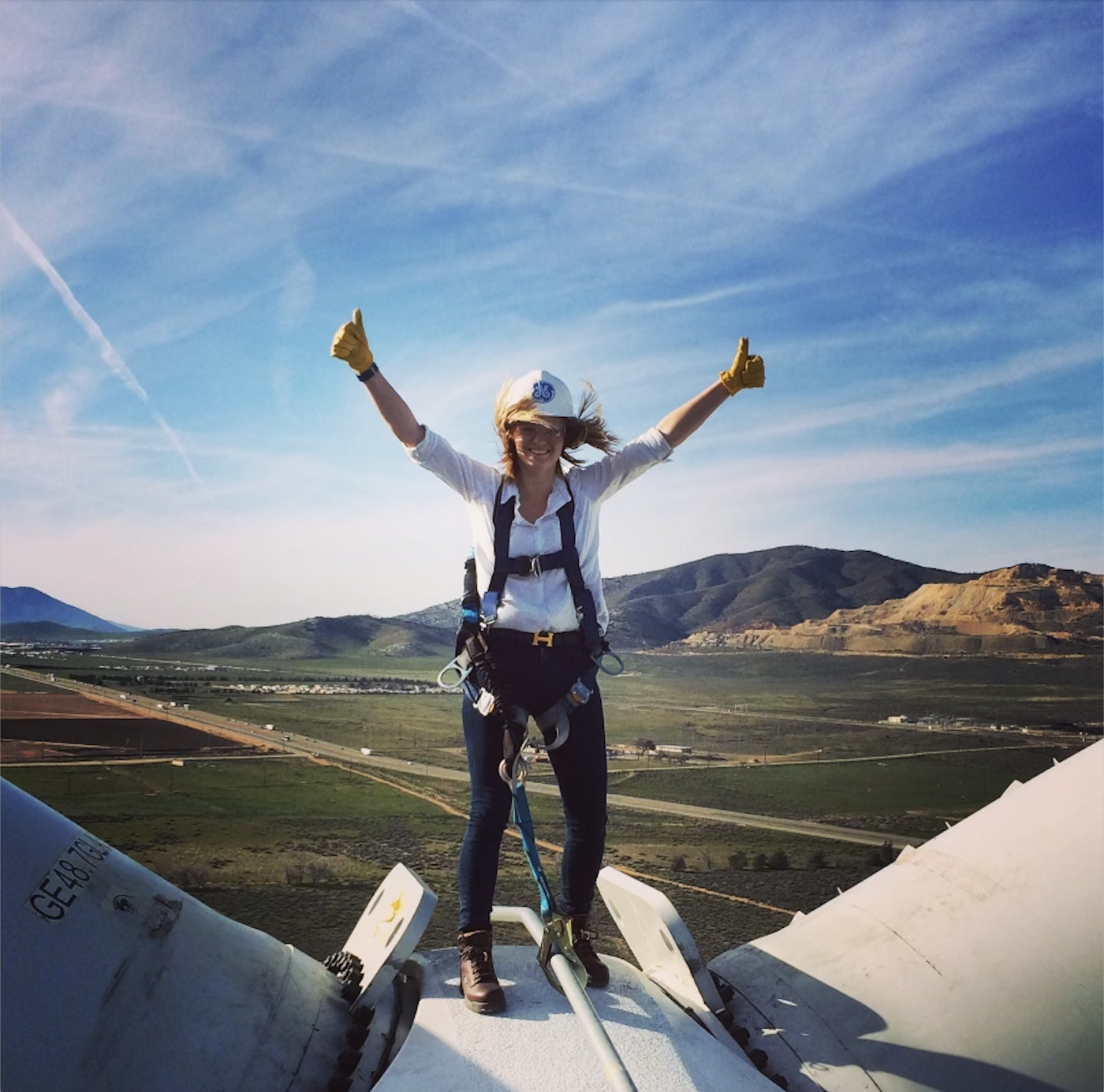 A blonde woman stands on top of a wind turbine with her arms raised