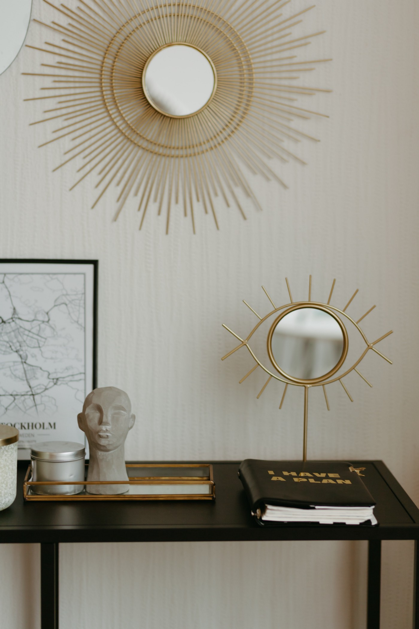 List of objects in this picture: Solar Disc Decor, Eyeball Mirror, Map of Stockholm, Sculptural Bust, Tins, Tray, Table, Wall, and A Book whose cover reads: I Have A Plan.