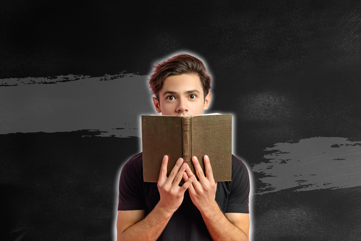 An amazed young man reading a book.