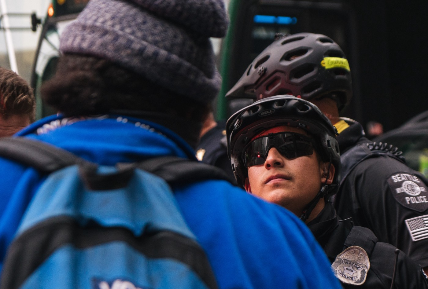One maskless Seattle police officer wearing sunglasses and a bike helmet attempts to stare down a protester.