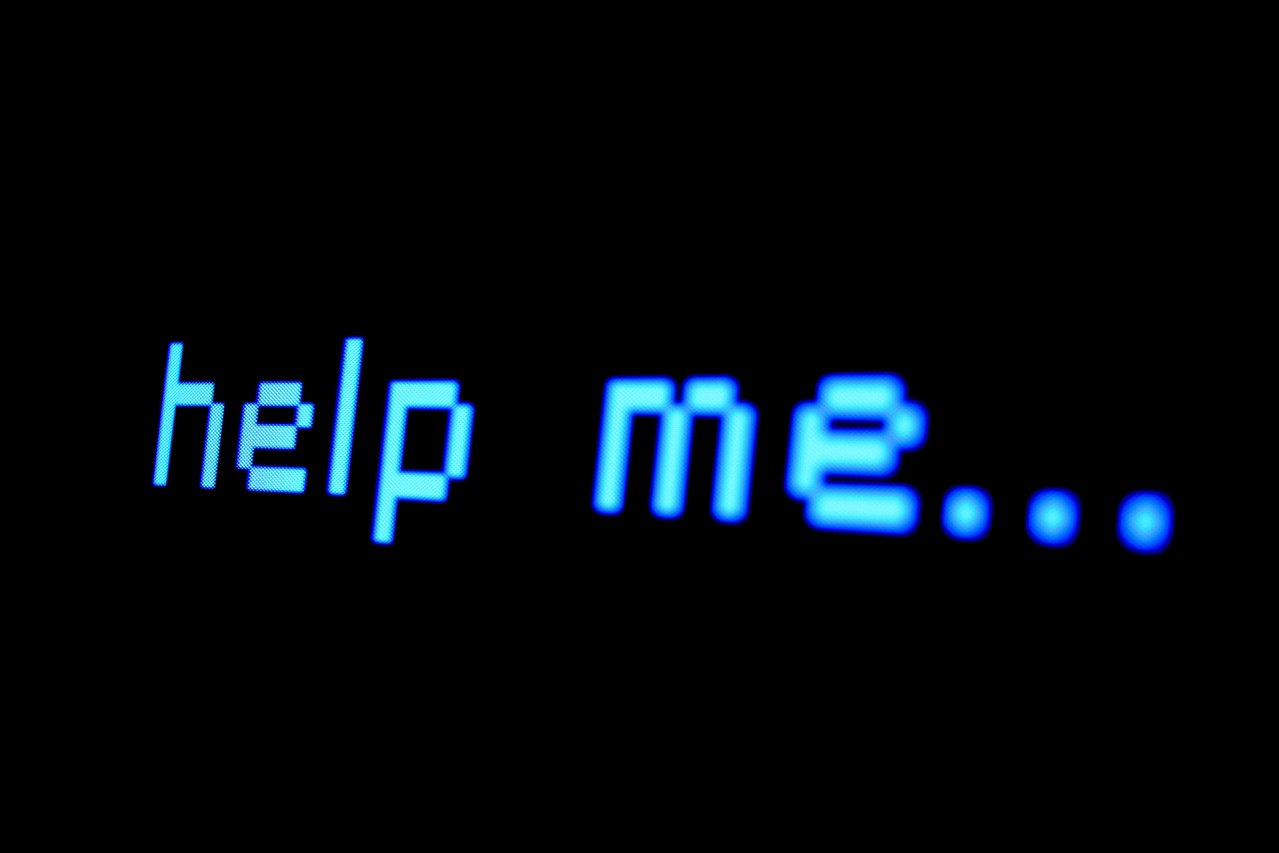 """A black computer screen with only the words """"help me…"""" written in blue, monospace font."""