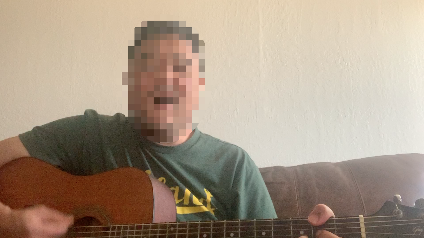Singer playing an acoustic guitar.