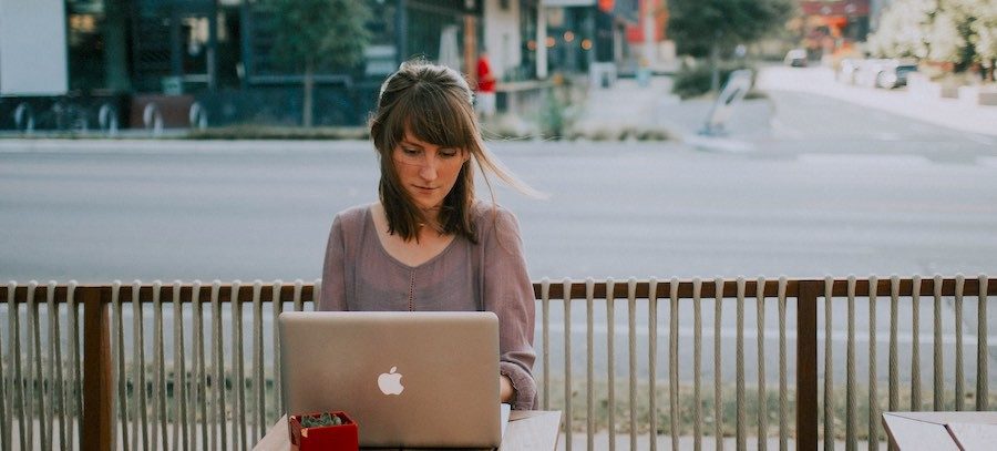 Young lady working outside on laptop