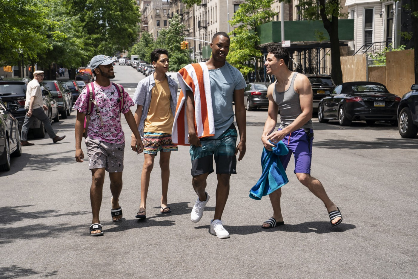 A scene from In The Heights featuring several characters standing on a road.