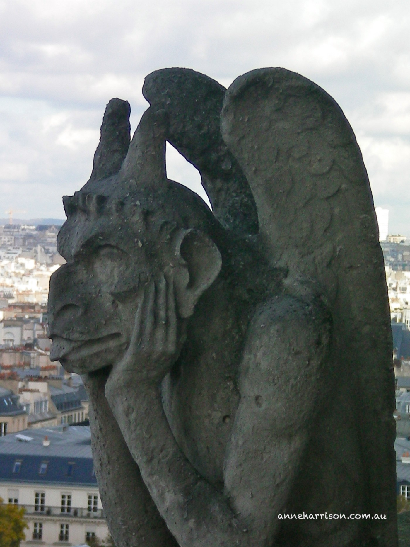 A gargoyle on Notre Dame resting his head in his hands.