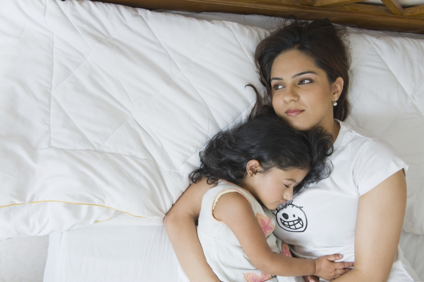 Tired South Asian mother holding her sleeping daughter.