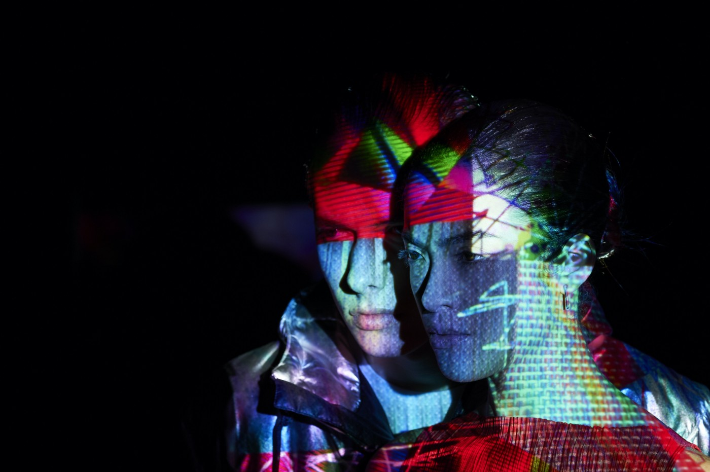 Two people standing close together in the dark with colorful, abstract shapes projected onto them.