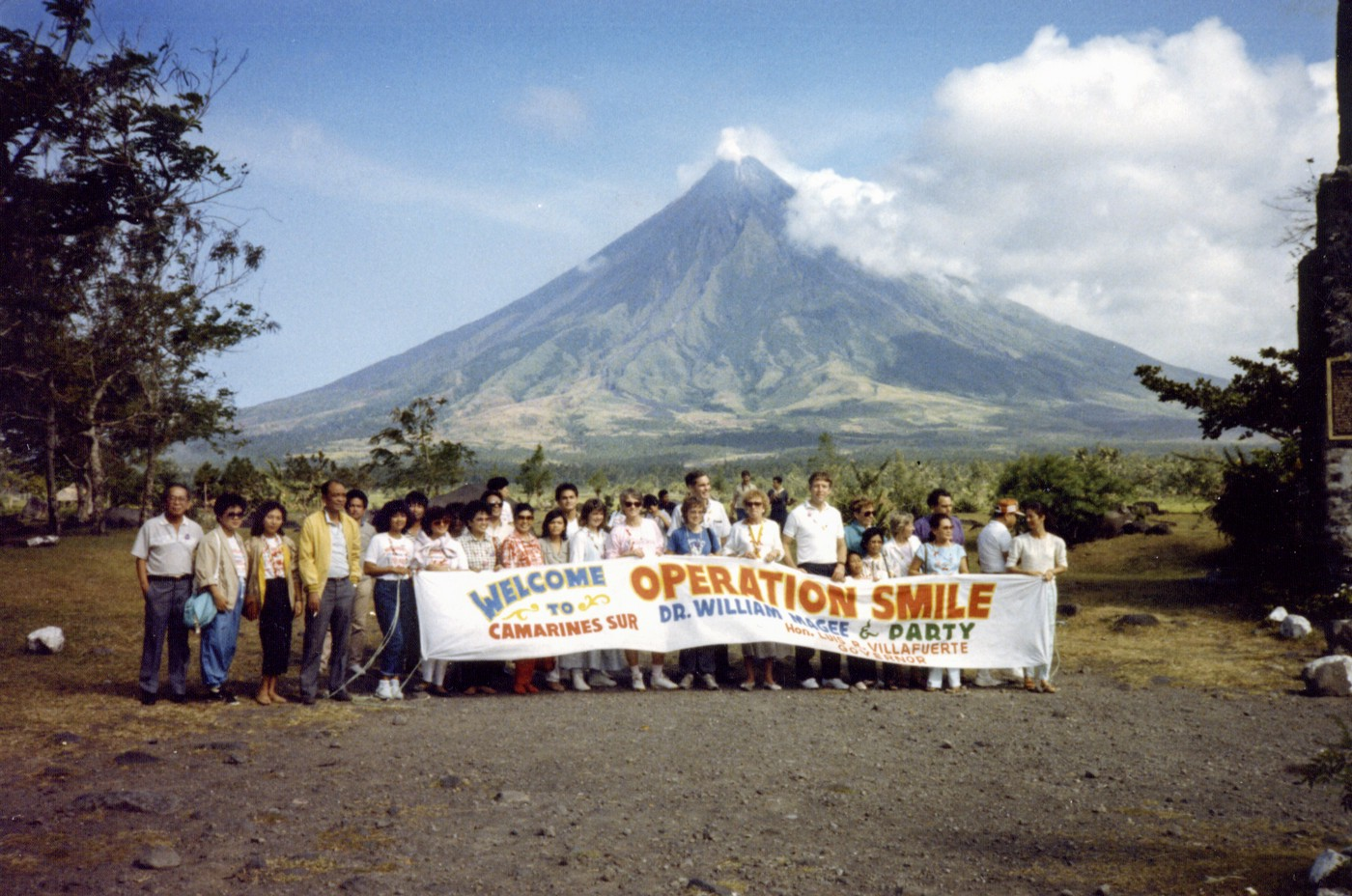 Operation Smile volunteers standing in front of a mountain in the Philippines holding a sign.