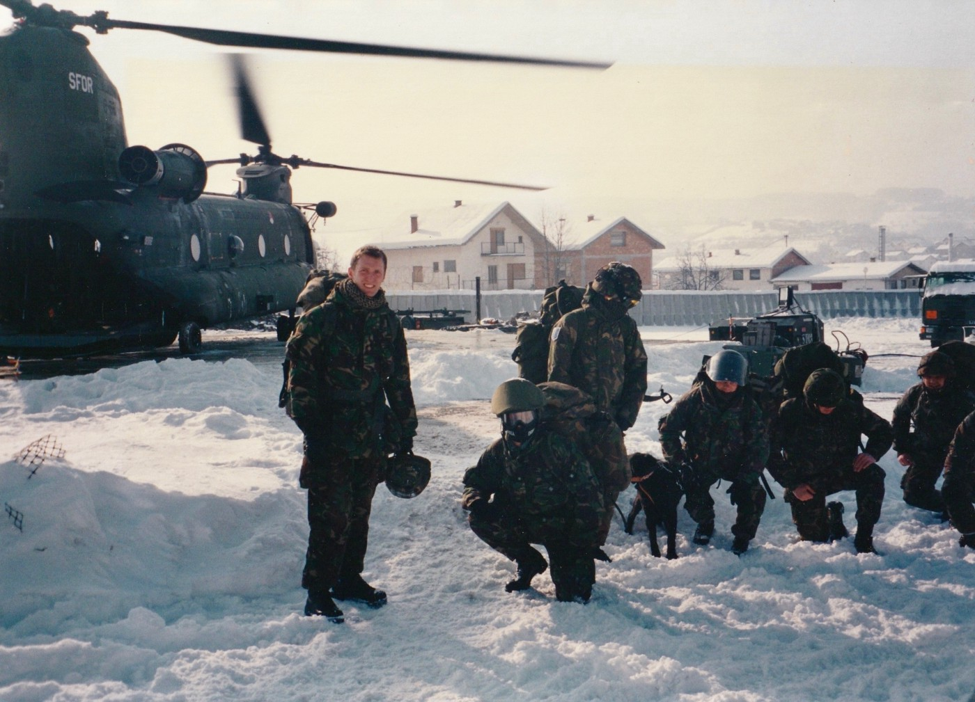 A photo of the author next to a helicopter in Bosnia.
