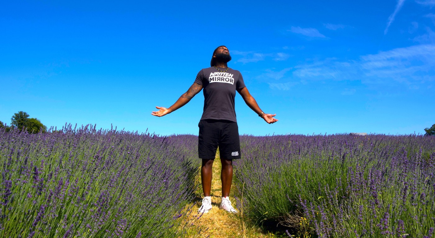 A man with his arms outstretched breathes in deeply in a field of flowers.