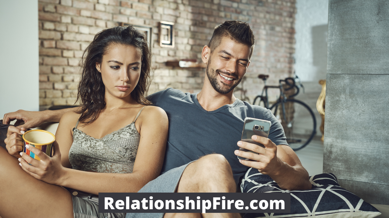 A woman looking jealous as her boyfriend smiles at a phone—How to not let jealousy ruin your relationship